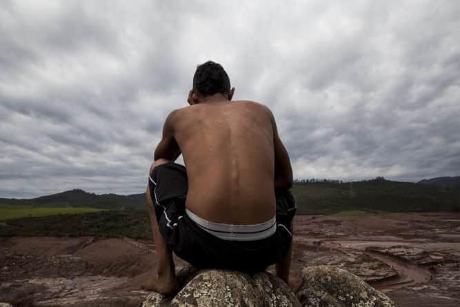 Rapaz sem camisa, de costas e abaixado, observa paisagem enlameada